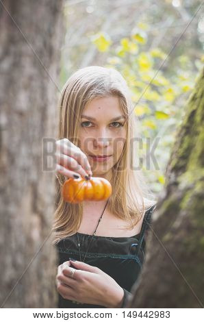 Blond long-haired girl in a fantasy black dress in an autumn forest scary halloween fairy tale