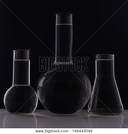 Laboratory Equipment, Three Glass Flask On Black Background