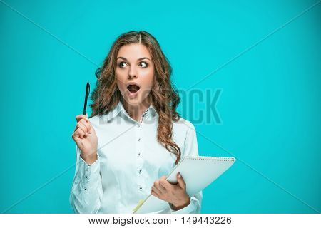 Surprised young business woman with tablet for notes on a blue background