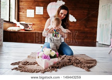 Young Happy Mother With Son Lying On Plaid Blanket