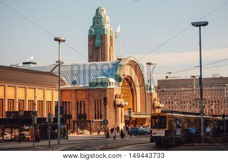 HELSINKI FINLAND - MARCH 17 2015: Tram is in front of the Railway station in Helsinki at sunrise. Finland