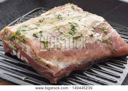 piece of raw marinated meat in a pan-grill
