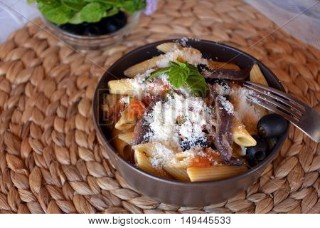 Delicious italian pasta penne with anchovies on a bowl on a table.