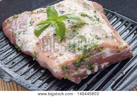 Piece of raw marinated meat in a pan-grill.