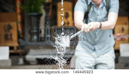 Foreign tourist takes water for purification at the entrance of Japanese temple