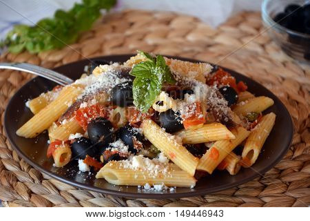 Delicious italian pasta penne with anchovies on a plate on a table.