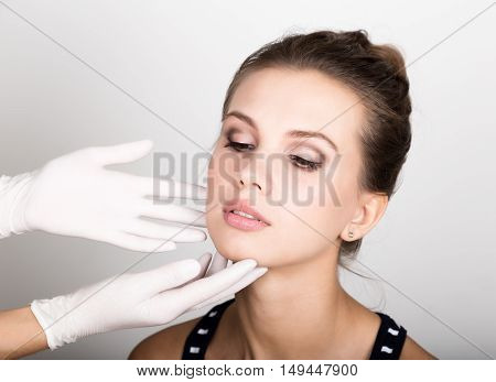 beautician hand's examining beautiful young female's face