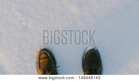 Brown leather shoes on snow in witner time