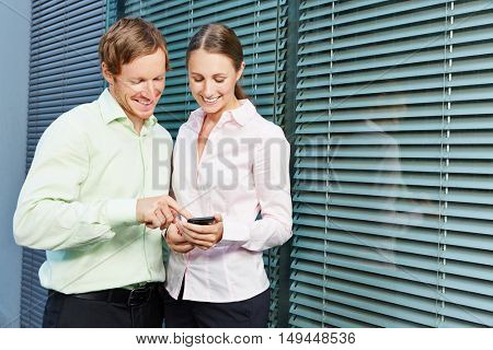 Two young business people using an app on a smartphone together