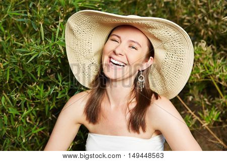 Happy woman with straw hat sitting in a green garden