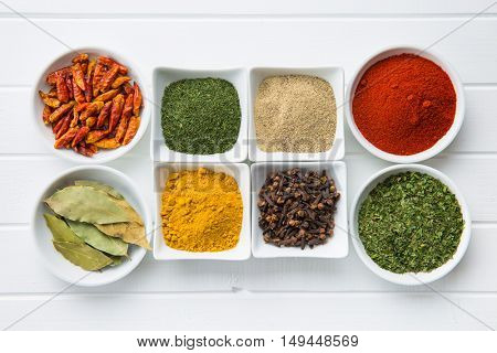 Various dried herbs and spices in bowl on white kitchen table.