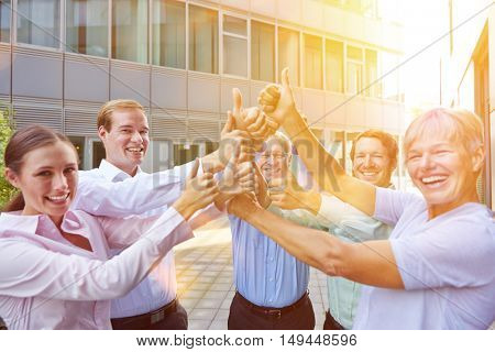 Happy business people team holding thumbs up in summer