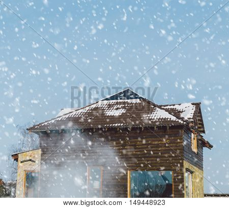 Wood house in village in snowfall time
