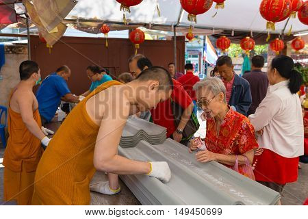 BANGKOK THAILAND - 8 FEB 2016: Monks Writing Messages on Underside of Roofing Panels at Wat Khanika Phon