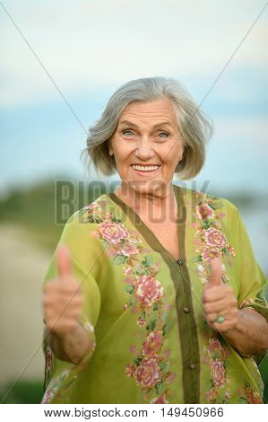 Elderly woman  in  summer near lake with thumbs up