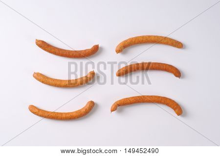 long thin sausages on white background