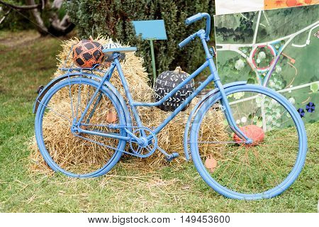 Blue bicycle with hay and pumkpins decoration, ar harvest festival in Moldova