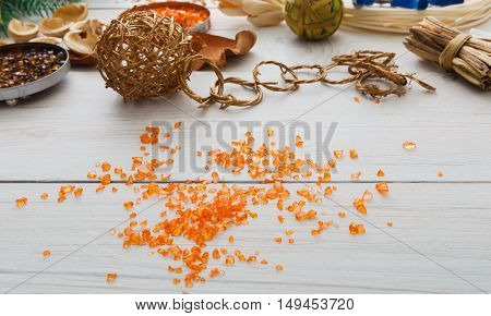 Creative diy craft hobby. Making handmade craft christmas ornaments and balls decorations. Closeup of trinkets at white wood background