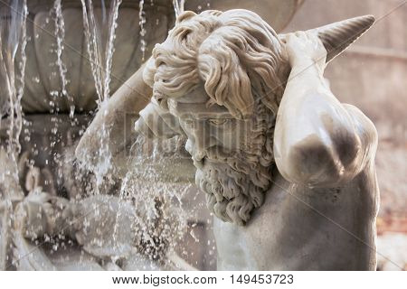 Catania, Sicily, Italy - JUL 25 2016: Detail of the Amenano fountain, in Catania, Sicily Italy. It Represents the Amenano river as a young man holding a cornucopia from Which flows out of the water
