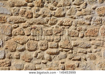 A sharp old stone wall in sunlight
