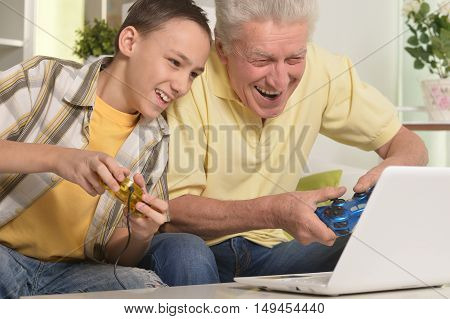portrait of  boy and  grandfather with a laptop, playing computer game at home