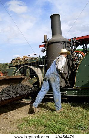 ROLLAG, MINNESOTA, Sept 1. 2016: An unidentified man shovels coal into the boiler of a Buffalo Springfield steam engine displayed at the annual WCSTR farm show in Rollag held each Labor Day weekend.