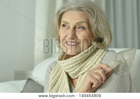 Portrait of elderly woman with flu inhalation