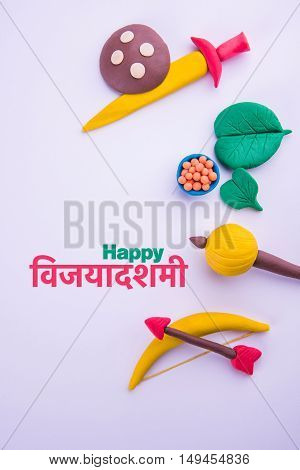 happy dussehra or happy vijayadashmi or happy aayudha pooja greeting card made using a photograph of colourful clay models of ancient indian armour used in Ramayana and Mahabharata