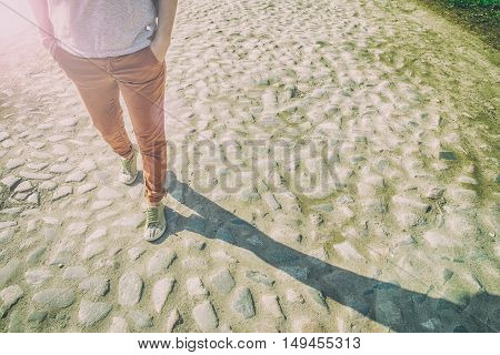 Woman walks in the spring sunny day on the old stone road and next to her goes shadow its