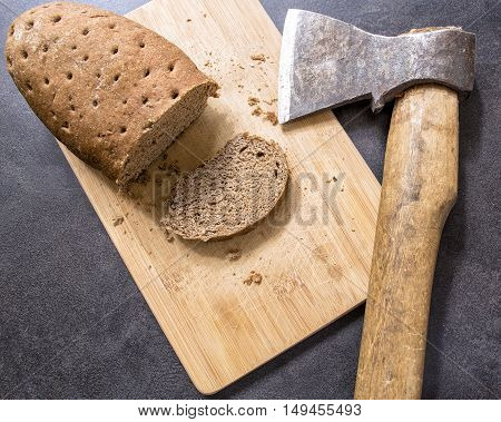 hard stale bread and cut off a piece of it lie on a wooden cutting board axe lying beside
