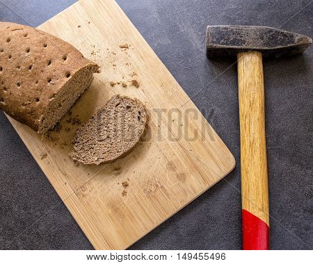hard stale bread and cut off a piece of it lie on a wooden cutting board hammer lying beside
