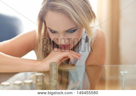 Happy blonde woman counting coin columns gold digger depth of field