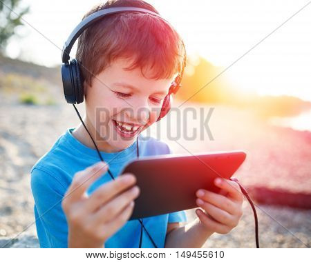 Happy little boy playing on tablet and laugh outdoor in sunset