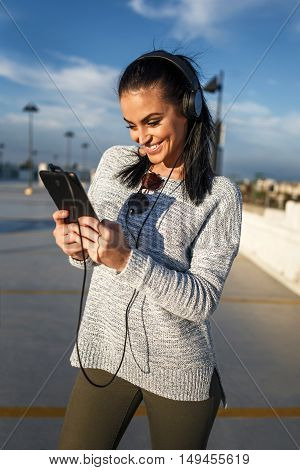 Happy woman with headphones listening music on tablet outdoor