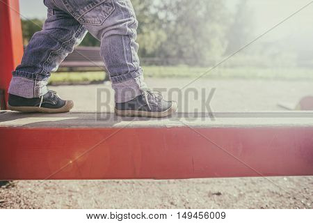two-year child goes on a wooden log on the playground and balances