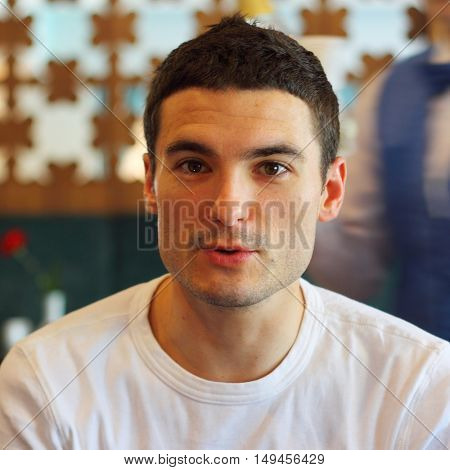 Handsome brown haired man headshot in a restaurant