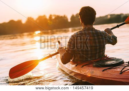 Meeting the perfect sunset. Rear view of young man kayaking on lake with sunset in the background