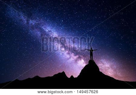Milky Way. Silhouette of a standing man with raised up arms on the top of mountain. High rocks mountain peak. Beautiful galaxy. Universe. Blue night starry sky. Night landscape with purple milky way