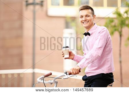 Young man in pink shirt with bicycle and cup of coffee on street