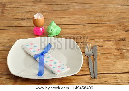 A simple easter place setting consisting of a plate knife fork and dot napkin tied with a blue ribbon and some easter table decorations.
