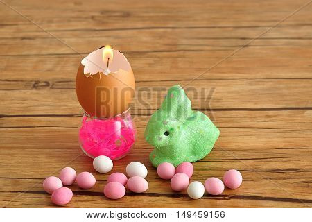 An empty egg shell that is turned into a candle displayed in a little container with a green bunny and pink and white candy for easter