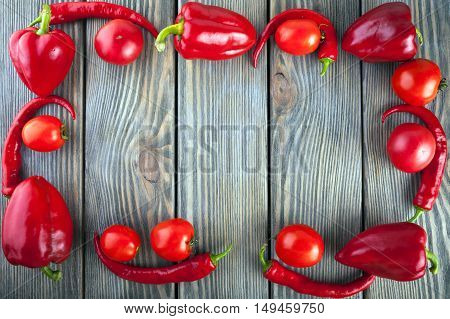 The set of red vegetables on wooden table, copy space image - tomatoes, pepper.