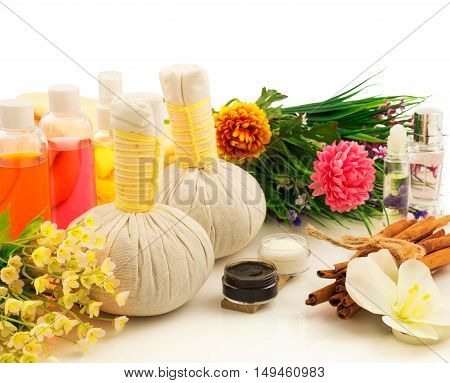 Spa compress balls, bottles of aroma oil, decorative flowers orchid, cream, bunch of cinnamon and green fresh plant