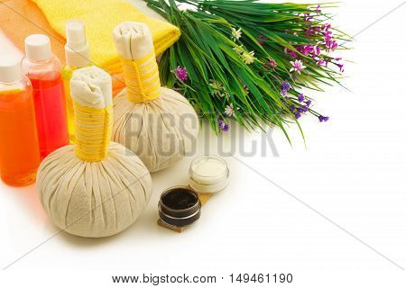 Spa compress balls bottles of color aroma oil decorative flowers cream yellow towels and green fresh plant