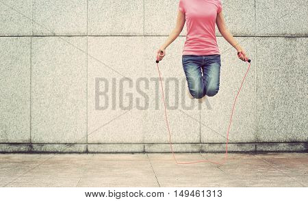 one young fitness woman jumping rope on city