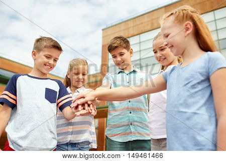 primary education, friendship, childhood and people concept - group of happy elementary school students with hands on top outdoors