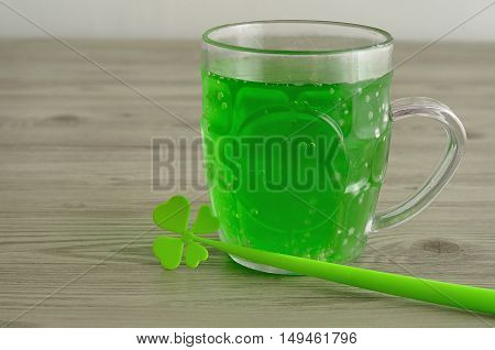 Green liquid in a beer mug displayed with a four leaf clover for St. Patrick's day