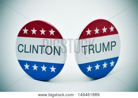 the names of Clinton and Trump written in a pair of campaign buttons with the colors and the stars of the flag of the United States, on a white surface, with a slight vignette added