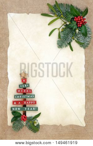 Christmas background border with old wooden tree, holly, ivy, mistletoe and snow covered fir on parchment over hemp paper.