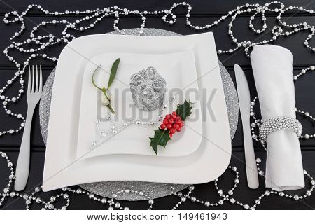 Christmas dinner decorative table setting with white porcelain plates, cutlery, linen napkin, holly, mistletoe and silver gift box and bead decorations over dark wood background.